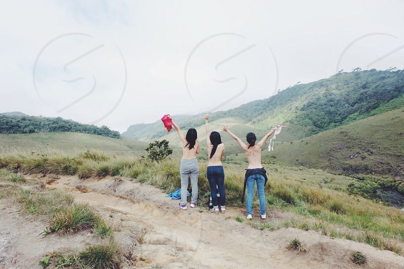 3 woman standing on dirt pathway photo