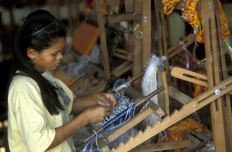 a weaving women working in a Farmer village outside of the city of phnom penh in cambodia in southeastasia.  photo