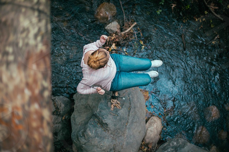woman in blue jeans sitting in a string near the gray rock photo