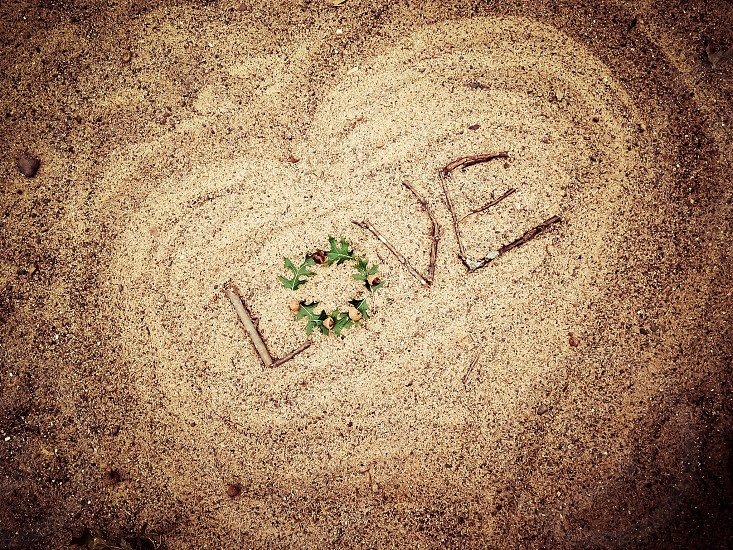 brown sand with wooden sticks forming love photo