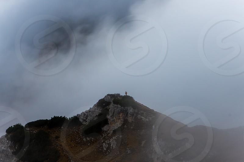 Man standing on rock in fog. photo