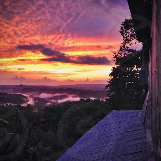 The sun sets over the Puerto Rican mountains- producers of some of the best coffee in the world.    Sunset mist clouds coffee photo