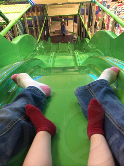person in blue denim jeans on green slide photo