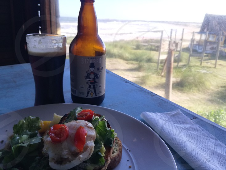 Toast with homemade bread guacamole rocket poached egg cherry tomato balsamic sauce... and breakfast stout with cocoa and coffee!! overlooking Playa La Viuda Punta del Diablo Uruguay 😍 photo
