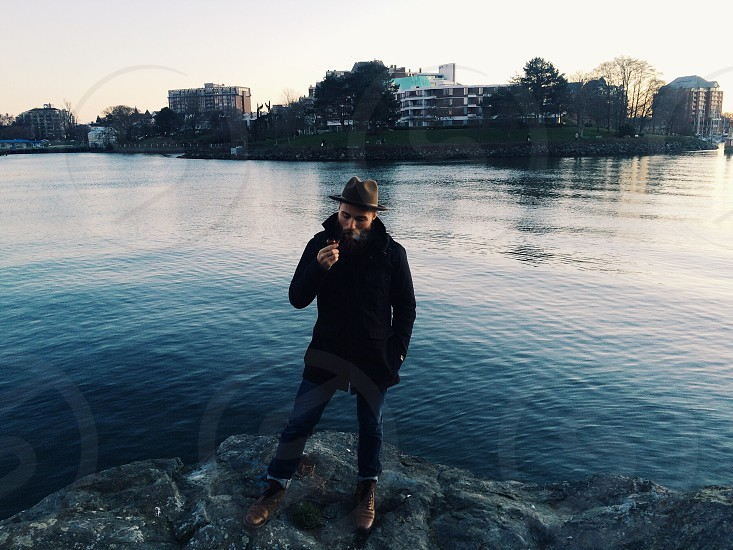 man in black coat and brown hat standing on rock on side of huge body of water during daytime photo