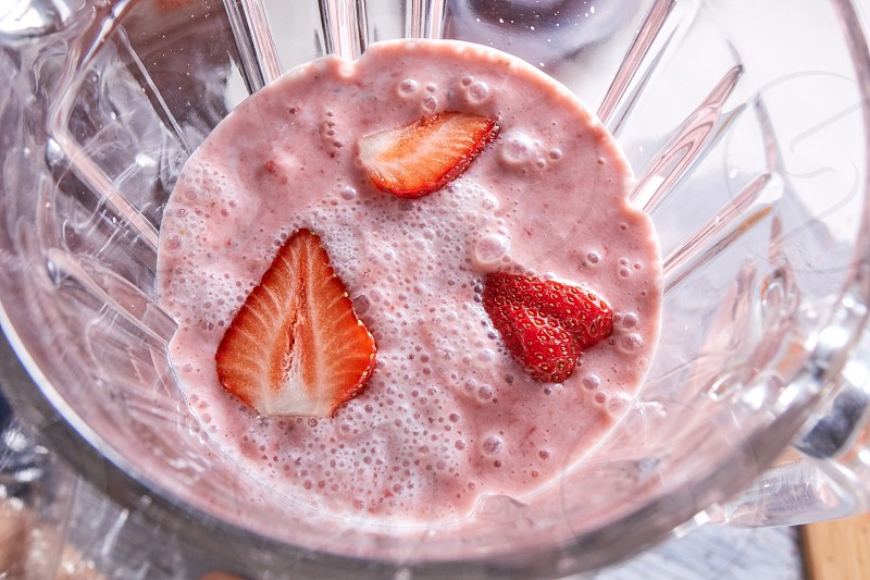 Homemade healthy smoothie dessert with strawberry pieces in a blender bowl. Top view photo