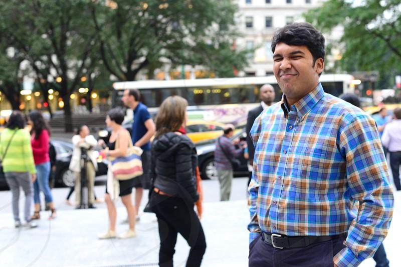 man wearing blue plaid collared shirt outside among peopel photo