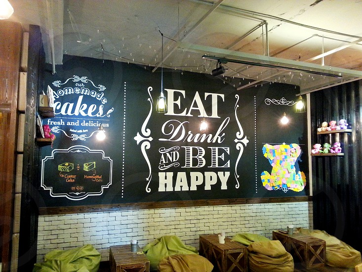eat drink and be happy wall signage below brown wooden table photo