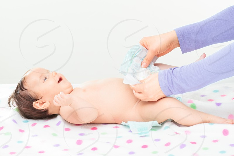 Mom changing diaper her little baby girl photo