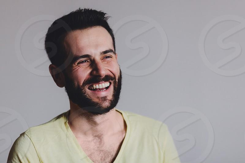Young bearded man laughing studio shot. photo
