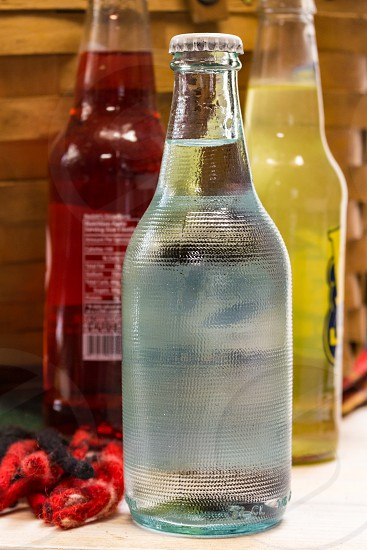 Water in a glass bottle with soda pop in the background photo