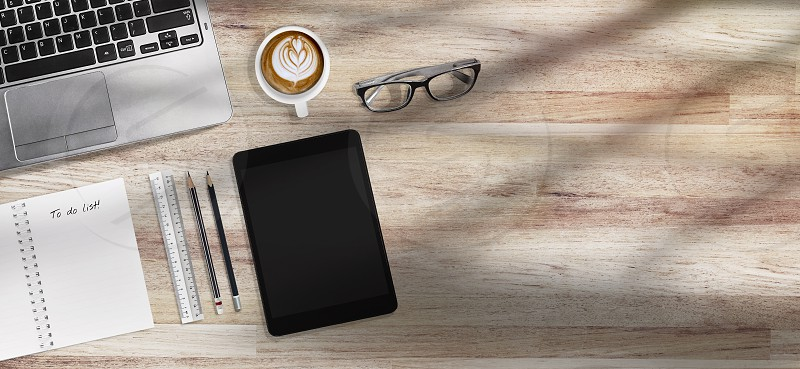 Coffee time concept design for banner Top view of modern office desk wooden table workplace with laptop tablet with office supplies glasses and coffee. Morning sun cast on table with copy space. photo