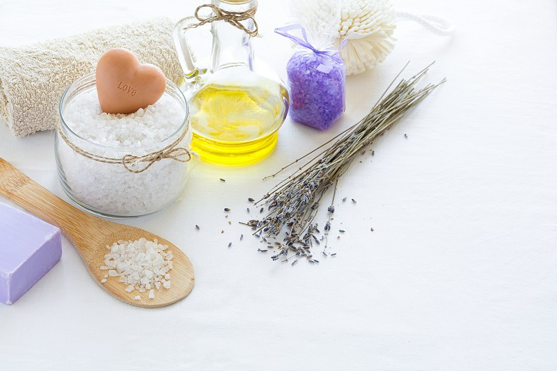 Wellness setting. Sea salt in glass soap towel olive oil and flowers on white textured background. Space for copy. Flat lay photo