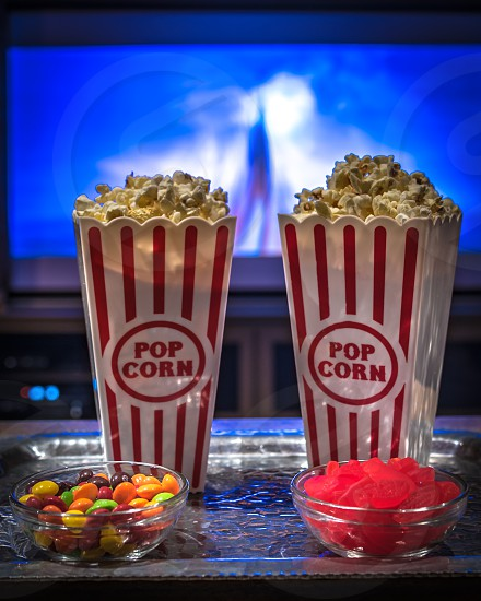 Popcorn and snacks on a metal tray in a home movie theater setting. Movie screen is blurred out in the background. photo