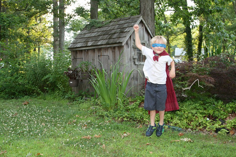 boy in blue mask and red cape jumping up outside near wood shed photo