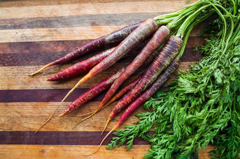 green vegetables healthy fresh home-grown carrots kitchen cutting board purple heirloom photo