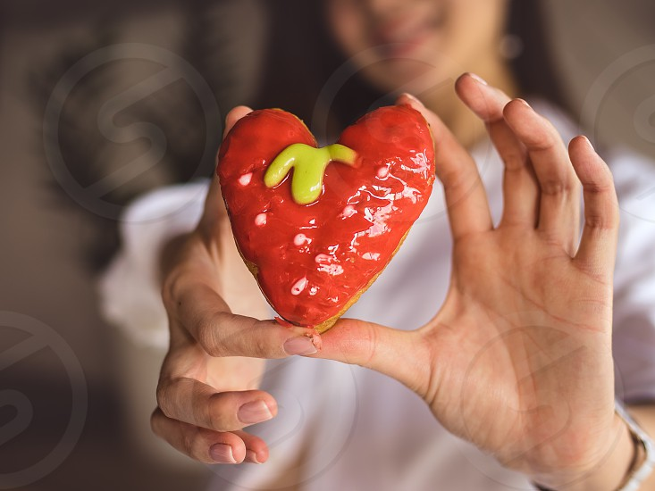 woman's hands keeping heart-shaped donut photo