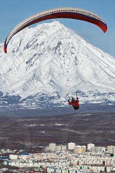 PETROPAVLOVSK-KAMCHATSKY KAMCHATKA RUSSIA - NOVEMBER 21 2014: Paraglider flying over Petropavlovsk-Kamchatsky City on the background of the active Koriaksky Volcano on a sunny day. photo