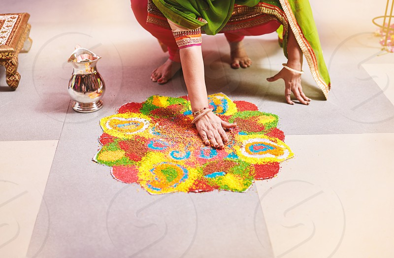 Women coloring tradition colorful rice art or sand art (Rangoli) on the floor with paper pattern using dry rice and dry flour with colored from natural pigments like sindoor haldi (turmeric) photo