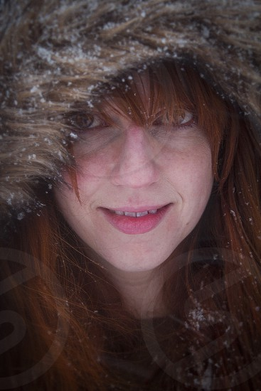 Red headed woman with hooded coat in the snow.  photo