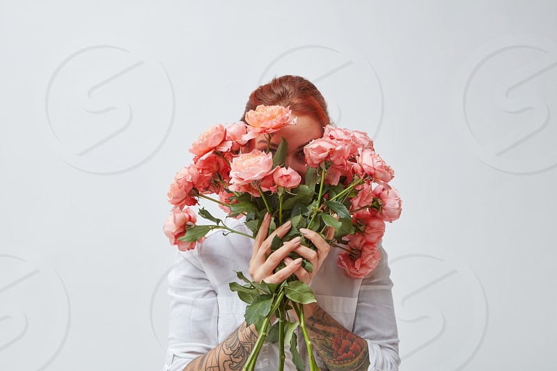 A happy woman with a tattoo on her hands hides her face behind a bouquet of fresh roses in a color of the year 2019 Living Coral Pantone. Postcards for Mother's Day. photo