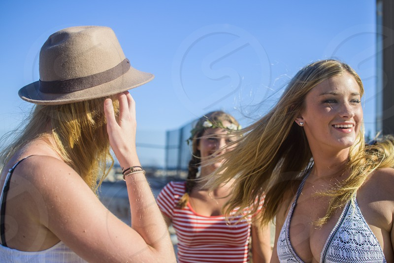 woman in blue and white halter bikini top woman in white and black top wearing brown fedora hat and woman in red and white stripe scoop neck shirt wearing floral crown photo