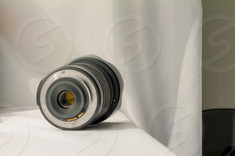 Black camera zoom lens on white cloth. photo