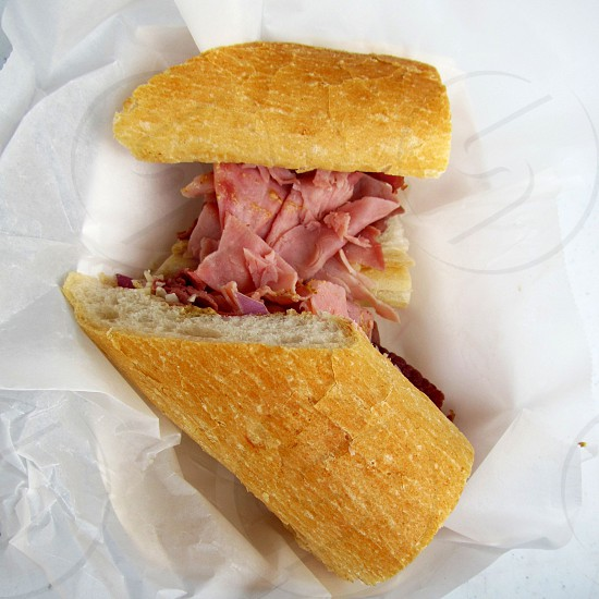 Ham poboy on French bread on white wax paper photo