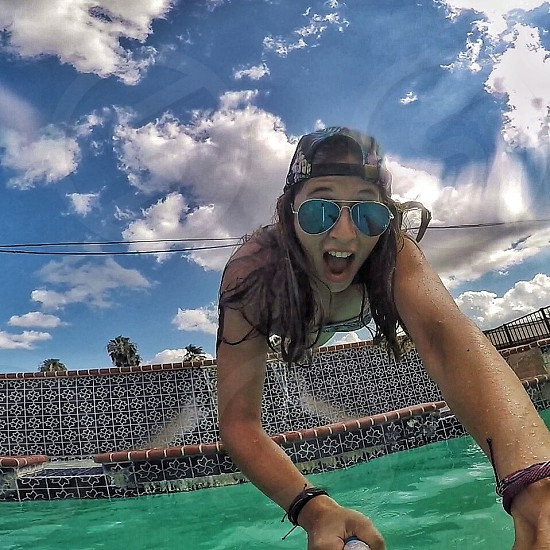 woman wearing silver-colored Aviator sunglasses on jumping on swimming pool photo