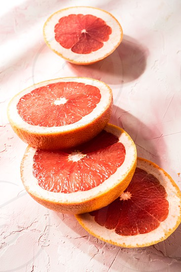 Sliced red grapefruit on a pink colored background photo
