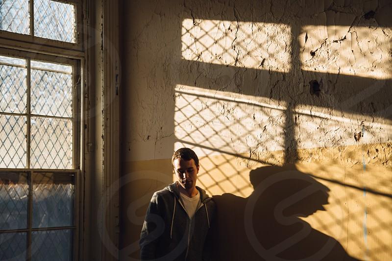 man in sweatshirt standing near window photo