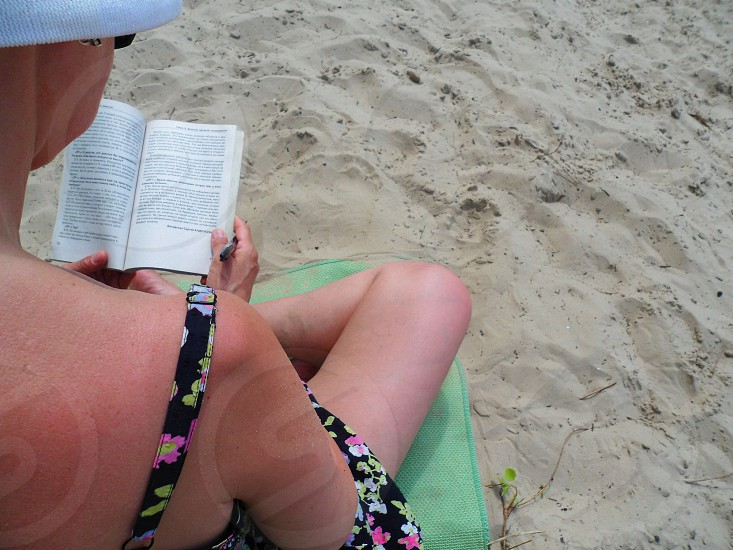 A girl in a sarafan sits on the sand and reads a book photo