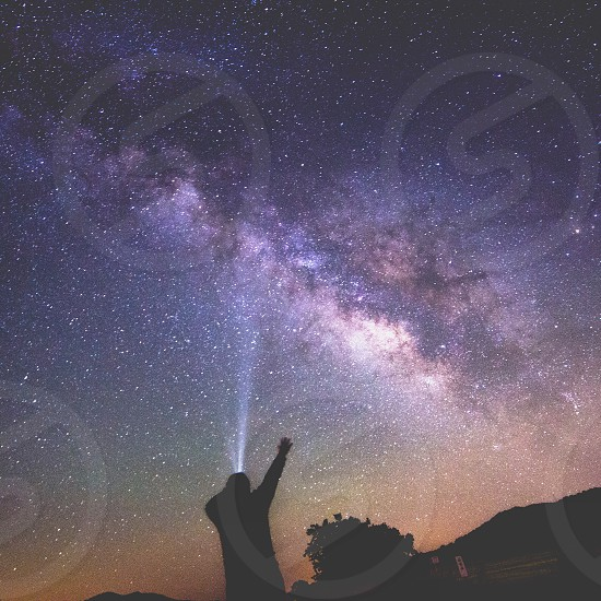 photography of silhoutte of person facing constellation on sky photo