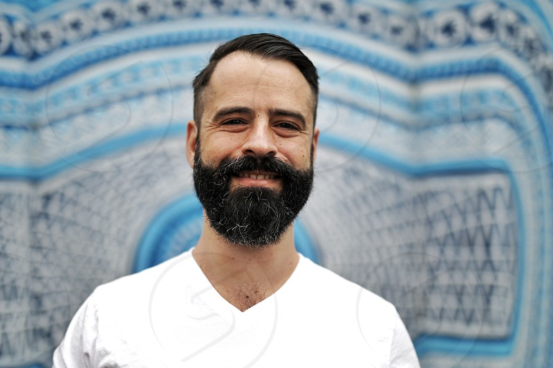 portrait man hipster beard bear sunny happy smile blue background photo