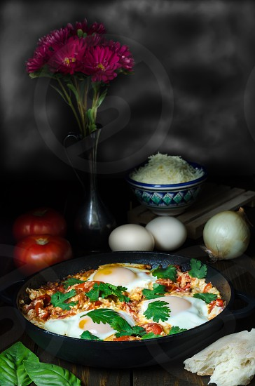 Turkish shakshuka on pan with ingredients on dark background photo