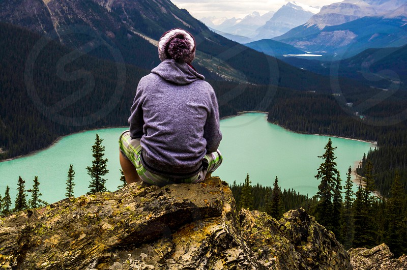 person siting on a rock in front of a lake photo