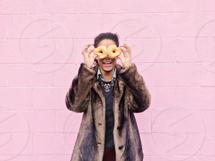 woman holding doughnuts over her eyes photo