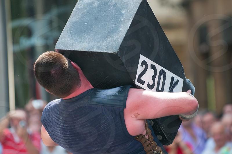 man lifting a 230k pound box photo