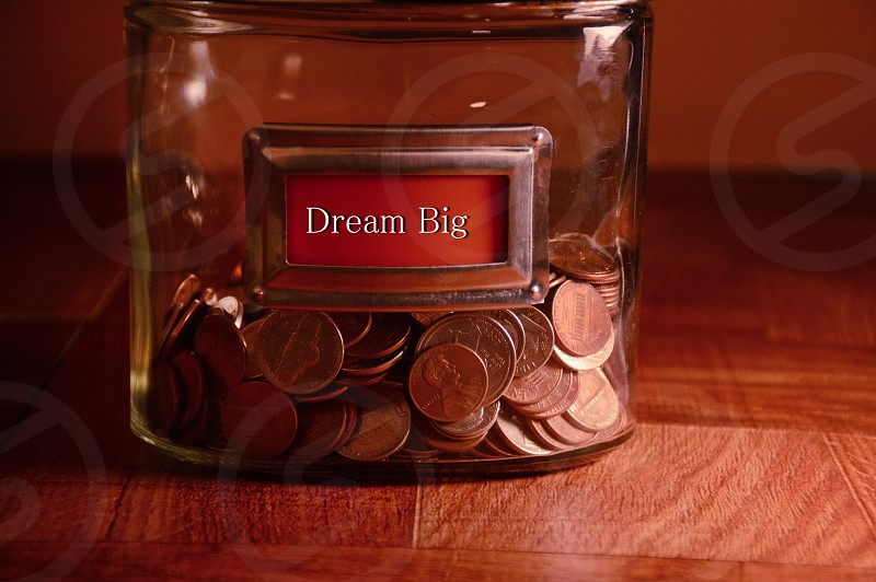 "glass jar labeled ""Dream Big"" saving several coins photo"