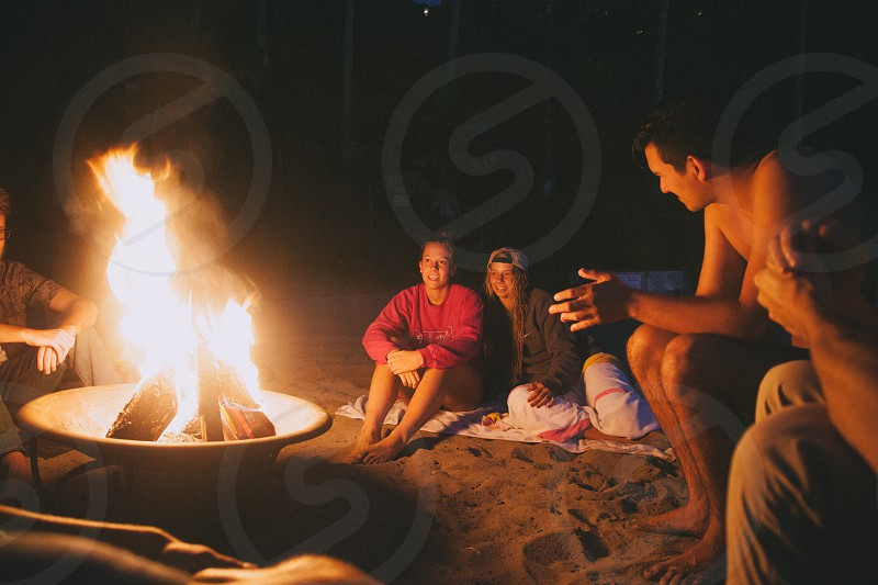 people sitting around a bonfire photo