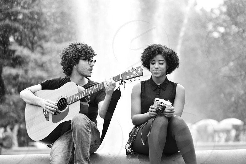 Washington square park new york city kids teens in love playing music by a water fountain black white photo