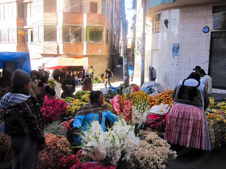 woman in blue long sleeved dress selling flowers photo