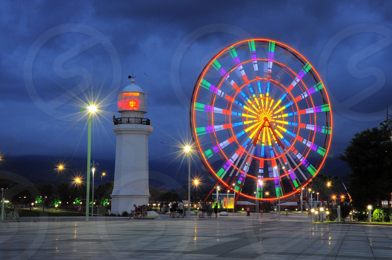 ferris wheel beside light house photo