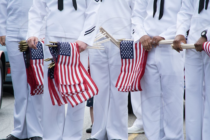 sailors in white dress clothes holding bunches of american flags miniature photo