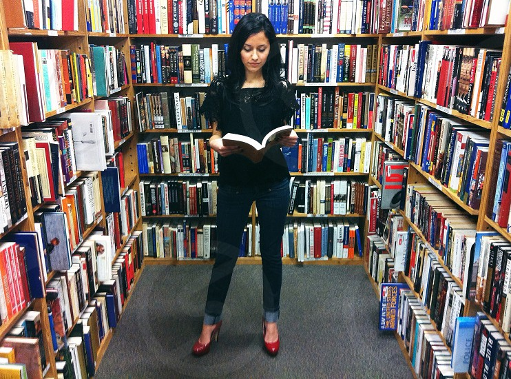 woman in black scoop neck shirt holding book inside library photo