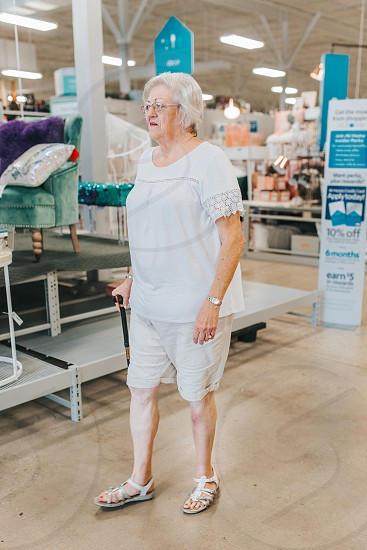 Elderly woman walking with her cane and going shopping photo