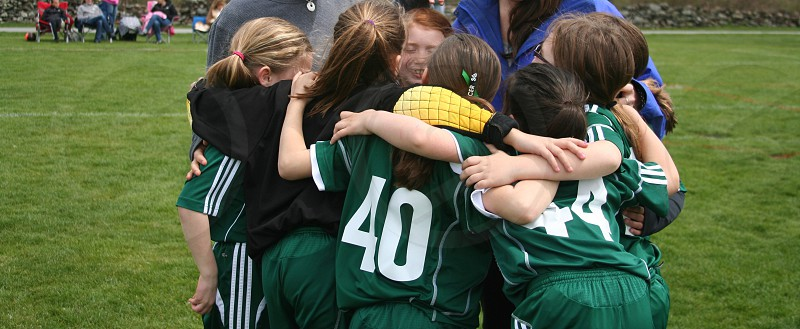 photo of girl's sports team hugging together at green field during daytime photo