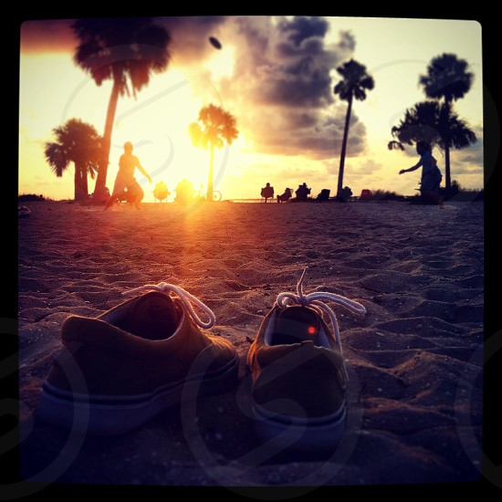 red low top sneakers on sand photo