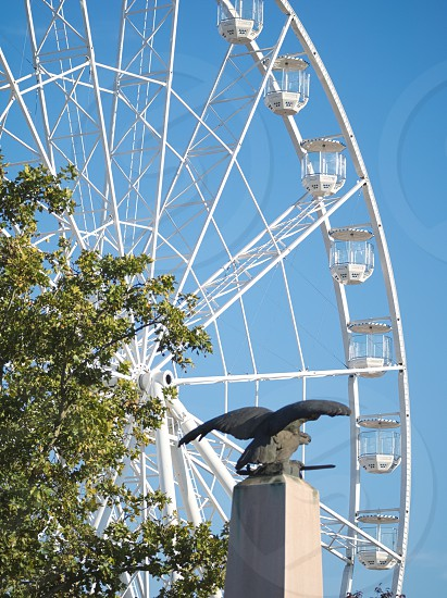 Empty White Ferris Wheel and Turul Statue Closeup in Győr Hungary photo