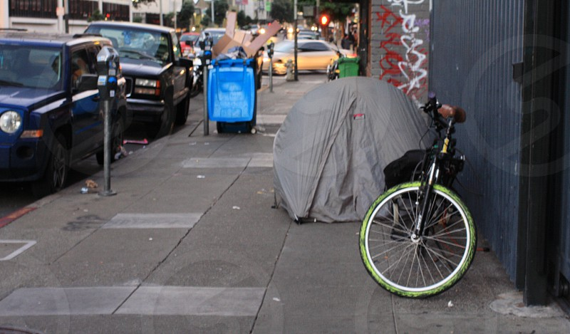 Homeless people sleeping in a tent on the street. Garbage in the background homeless camp. photo